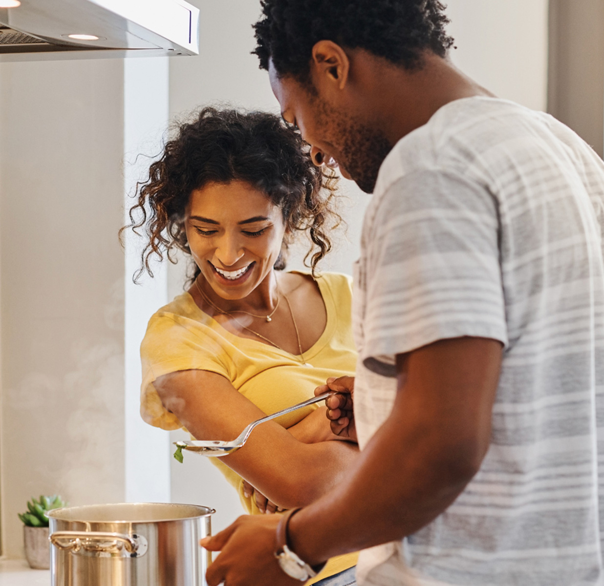 A happy couple in their kitchen cooking in their real estate property